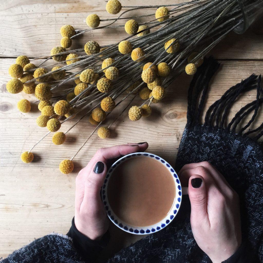Dear January, Hot mug of tea in hands with Craspedia