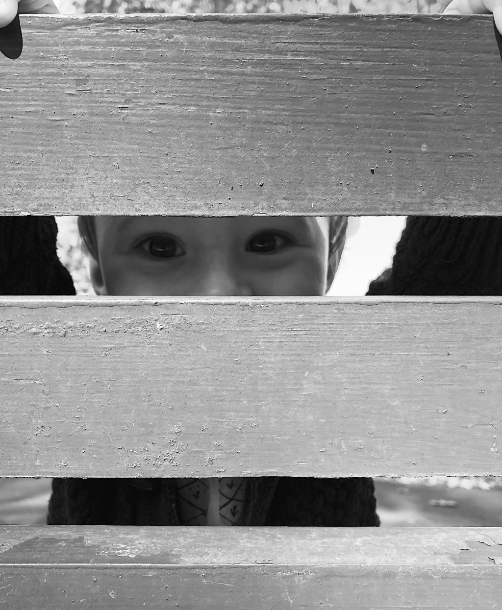 Black and whit portrait of a 10 month old baby peeping through park bench