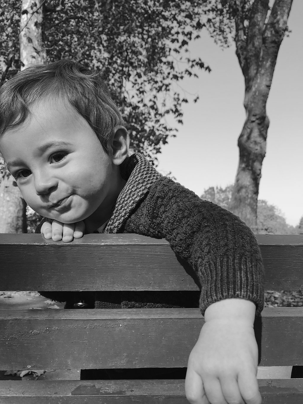 Black and whit portrait of a 10 month old baby leaning over park bench